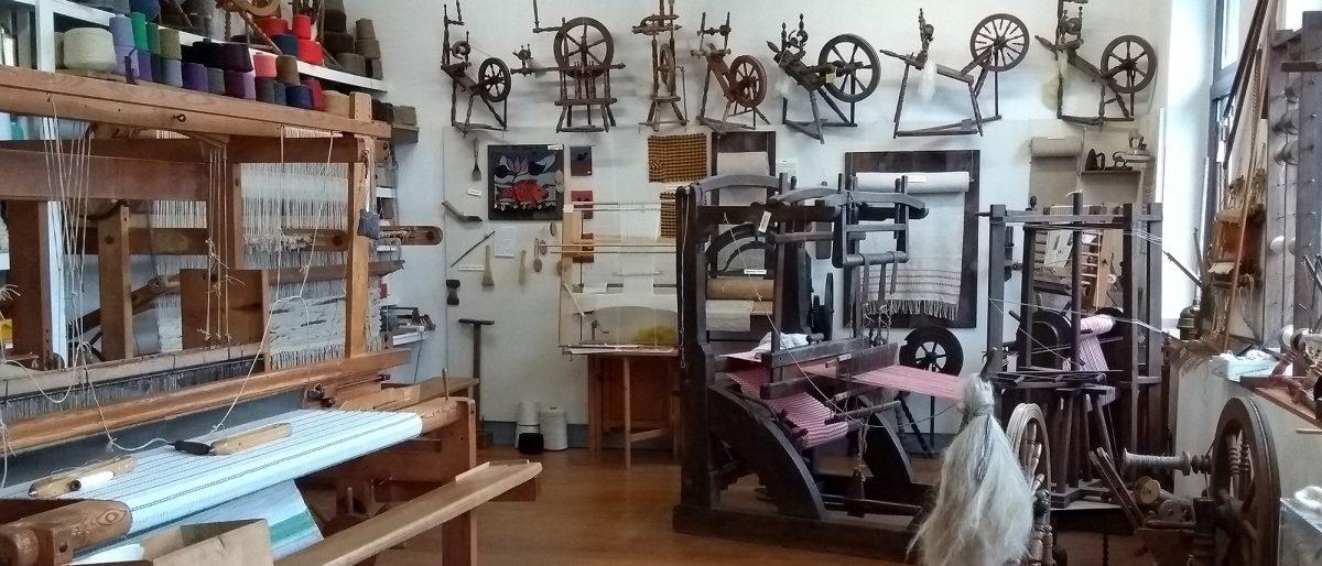 Werkstattraum mit Spinnrädern und Webstühlen