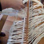 Fäden werden in das Riet sortiert